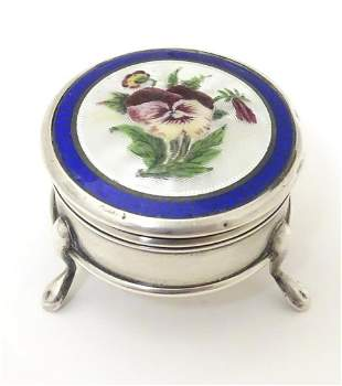 A silver pill box with Suffragette pansy enamel