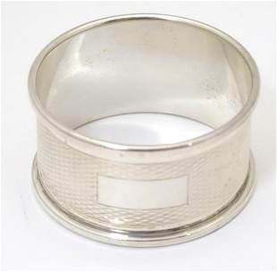A silver napkin ring with engine turned decoration,