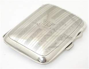 A silver cigarette case with engine turned banded