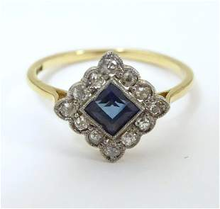 An 18ct gold ring set with central sapphire bordered by
