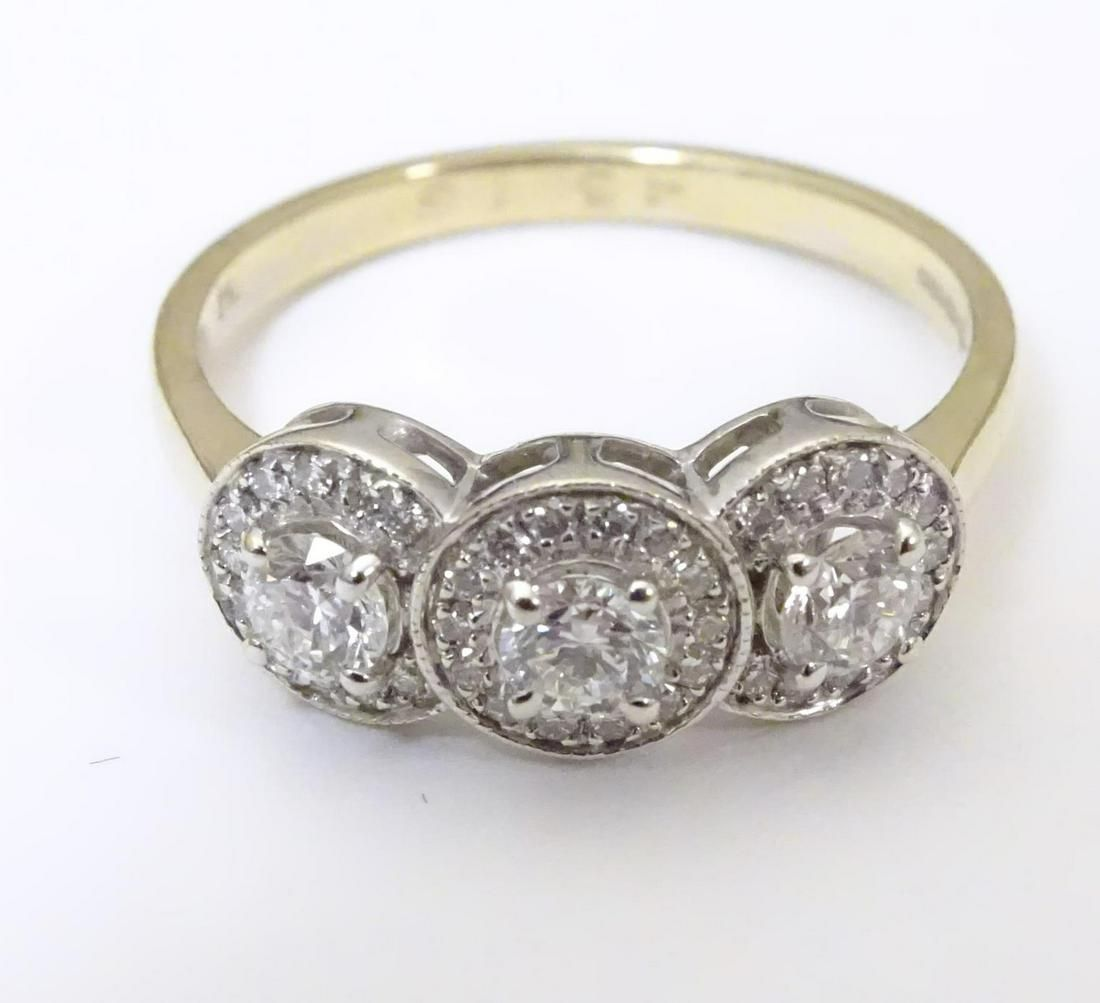 An 18ct gold ring set with tri of diamonds bordered by