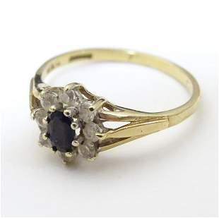 A 9ct gold ring set with central blue spinel bordered