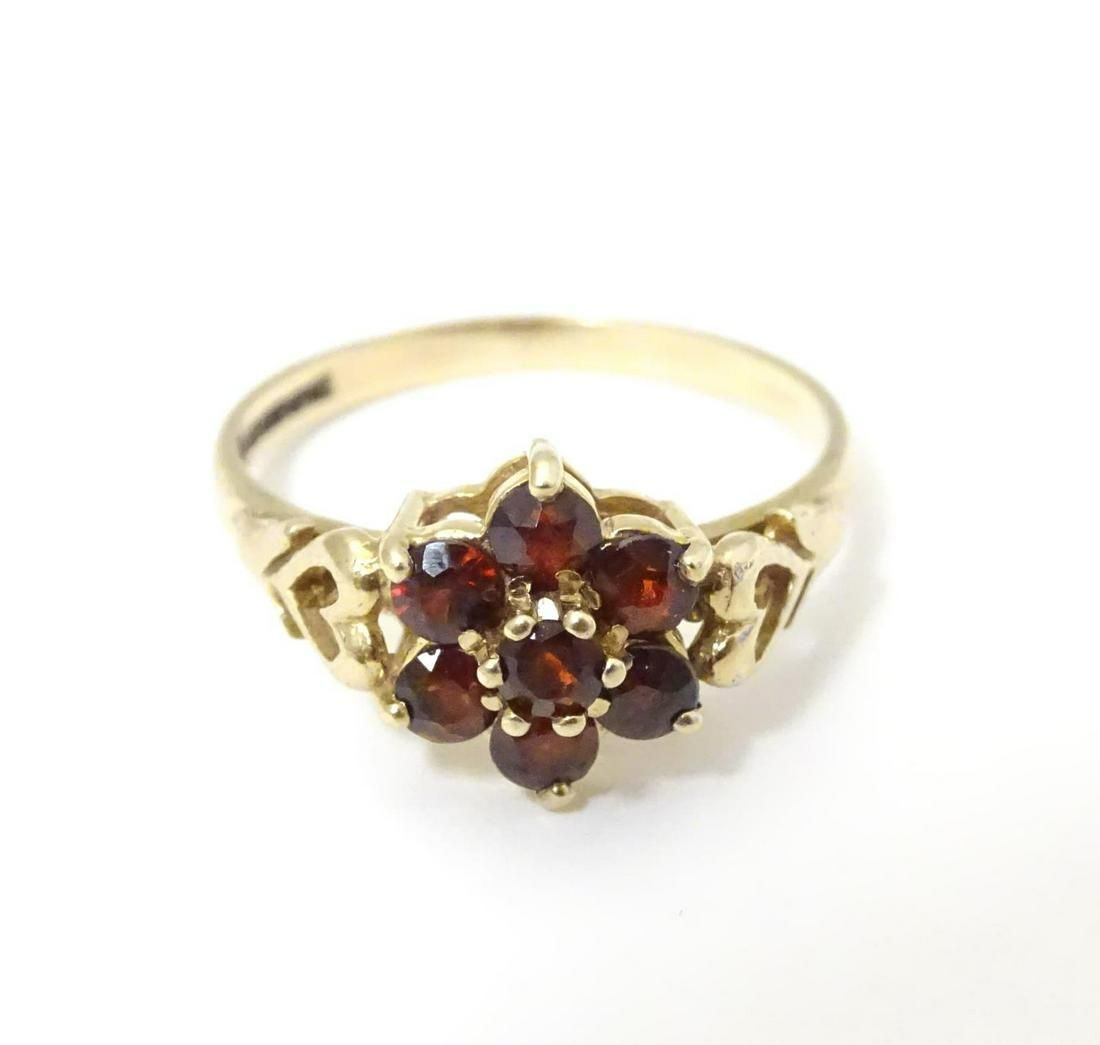 An 18ct gold ring set with garnets, diamonds and seed