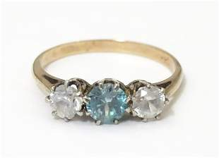A yellow metal ring set with topaz coloured central