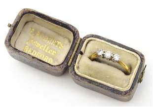 An 18ct gold ring set with trio of diamonds in a