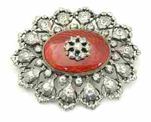 A silver brooch set with white stones and red guilloche