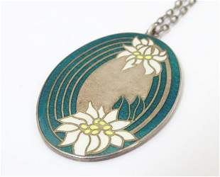 A silver pendant of oval form with floral enamel