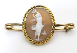 A yellow metal bar brooch set with shell carved cameo.
