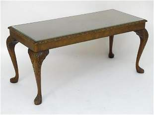 A mid 20thC walnut coffee table with a carved surround