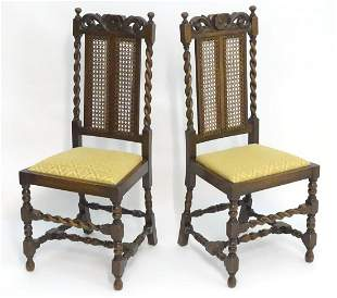 A pair of early / mid 20thC oak chairs with carved