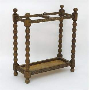 An early 20thC carved oak umbrella / stick stand with