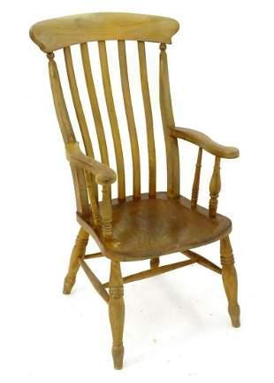 An early 20thC lathe back open armchair with an elm