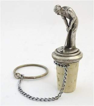 A 20thC white metal bottle stopper surmounted with a