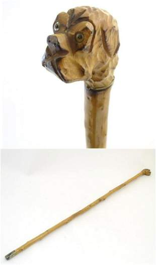 A 20thC walking cane with carved dog head handle.