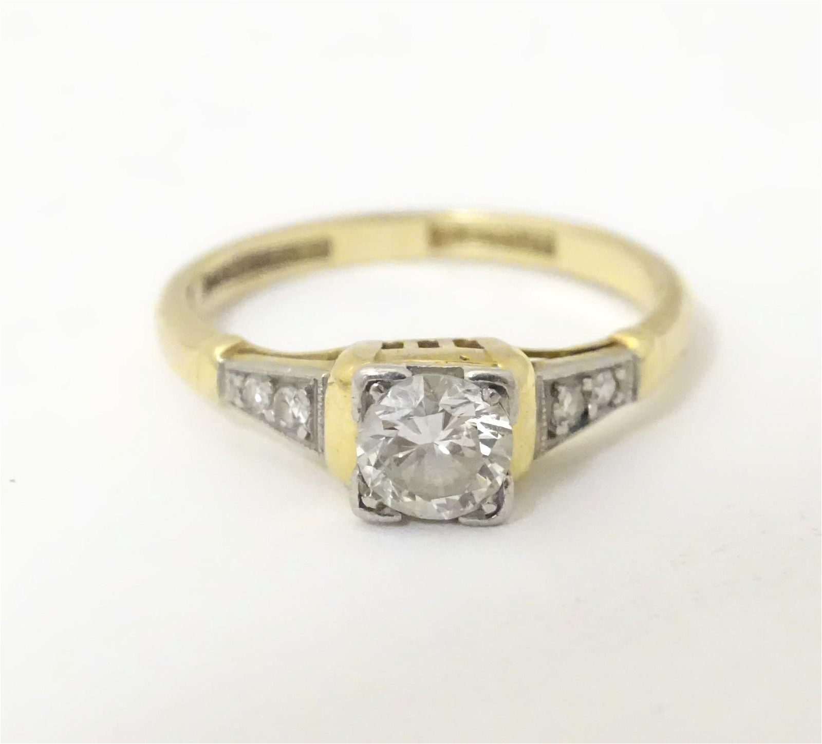 An 18ct gold ring with platinum set central solitaire