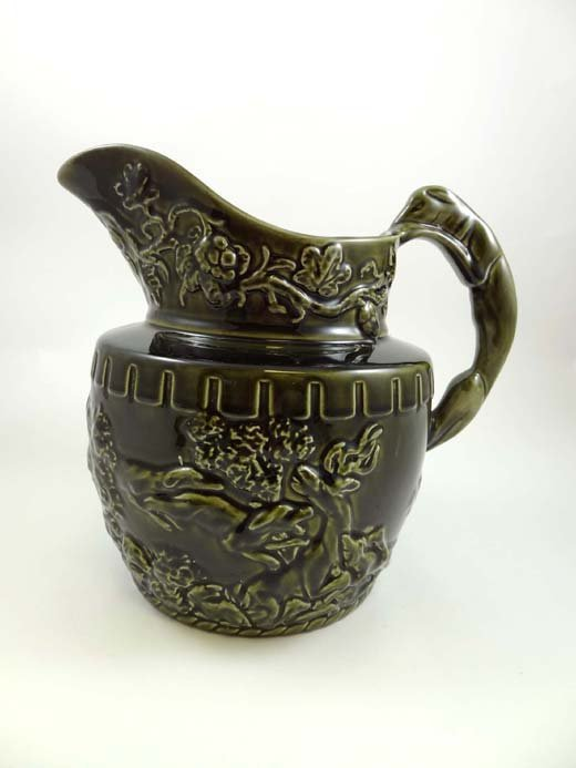 360: A late 19thC Arthur Woods green glazed jug moulded