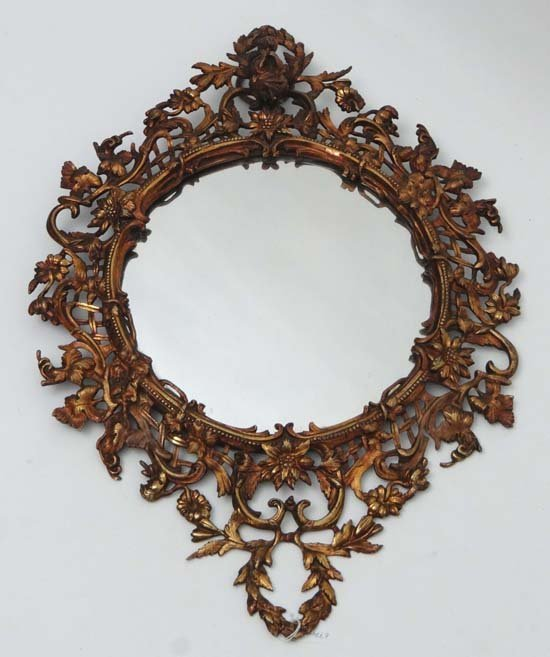 A c.1900 fire gilt framed wall mirror with foliate flor