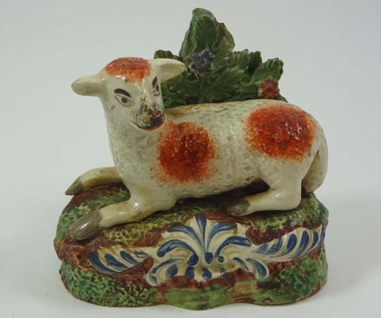 An early 19thC bocage figure of a recumbent sheep on a