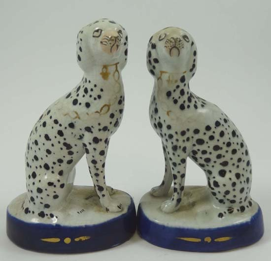A pair of 19thC pottery seated Dalmatians wearing gilt