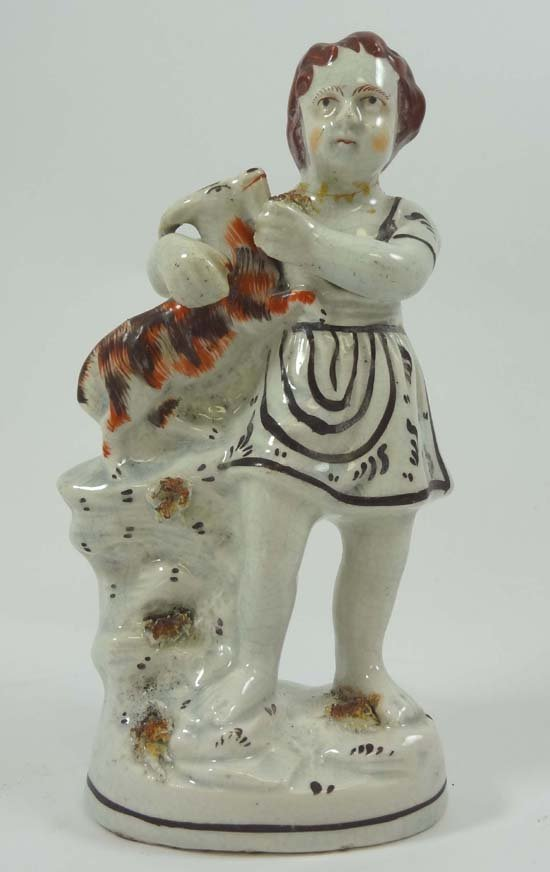 A Victorian Staffordshire figure depicting a young boy
