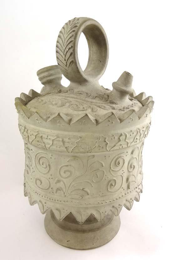 A white stoneware wine bottle having carved decoration