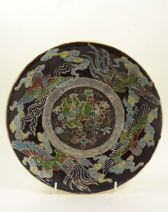 An Oriental shallow bowl decorated with dragons and exo