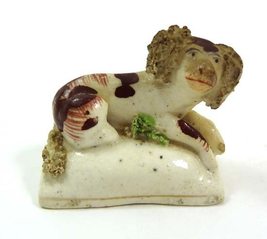 A 19thC Staffordshire porcelain figure of a recumbent s