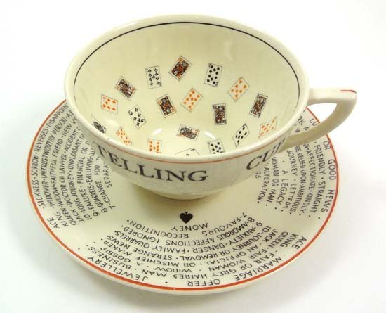 A Meakin pottery fortune telling cup and saucer decorat