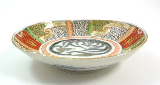 A polychrome Oriental shaped dish decorated with foliat