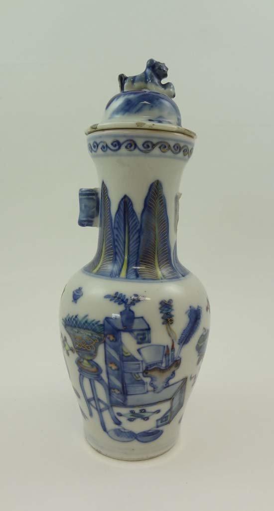 A Chinese long necked vase of baluster shape with dog o