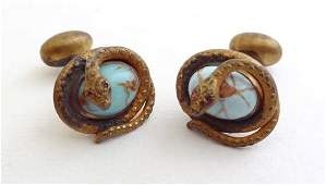 A pair of gilt metal cufflinks set with coiled snakes a