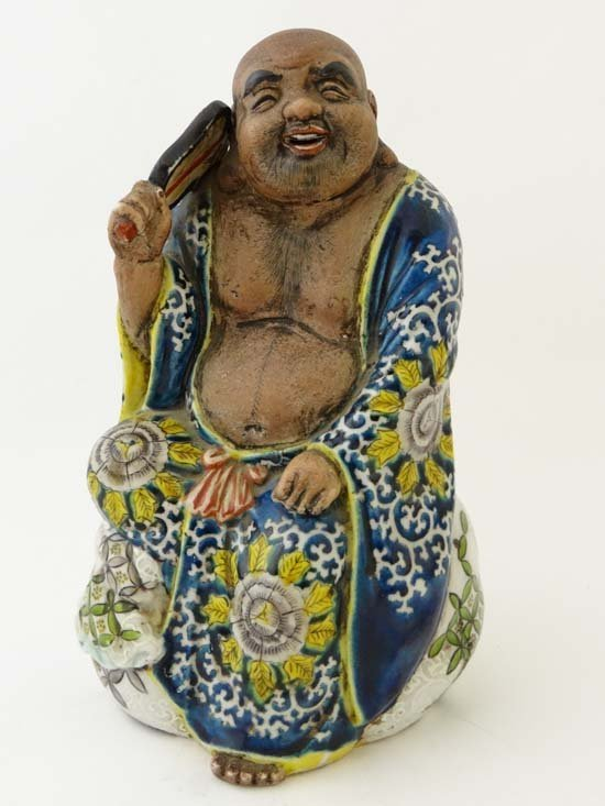 An Oriental hand enamelled figure of a seated Buddha