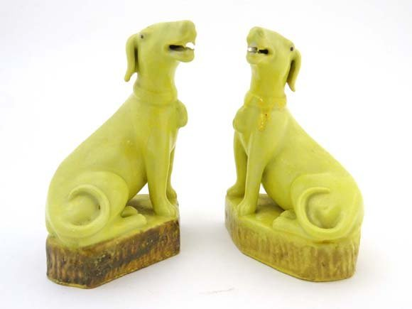 A Chinese pair of seated yellow glazed dogs moulded wit
