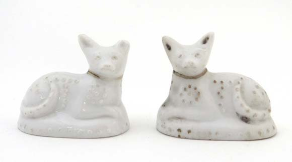 A pair of late 19thC white porcelain recumbent cats dec