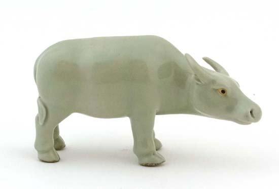 A Chinese celadon glazed model of a standing buffalo
