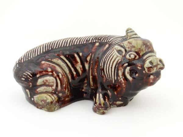 A Chinese pillow figure of a recumbent pig decorated in
