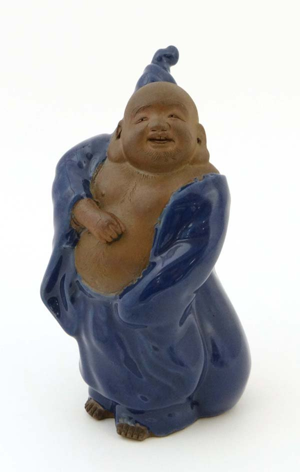 A Bizan Hotei figure, biscuit finish to body and blue