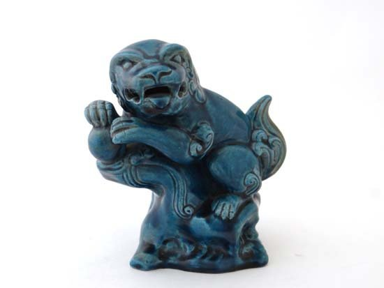 A Oriental turquoise glazed temple dog of fo holding a