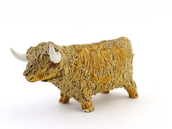 A pottery figure of a Highland cow decorated with honey