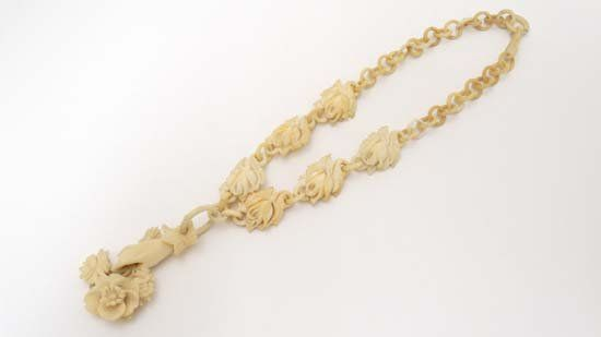 A c.1900 carved ivory necklace with pendant formed as a