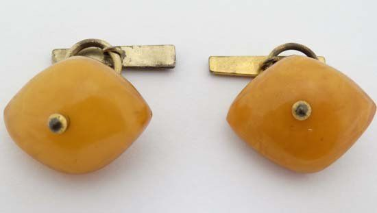 A pair of gilt metal cufflinks set with butterscotch co