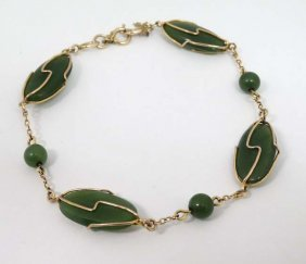 A Gold Bracelet Set With 3 Jade Like Beads And Four