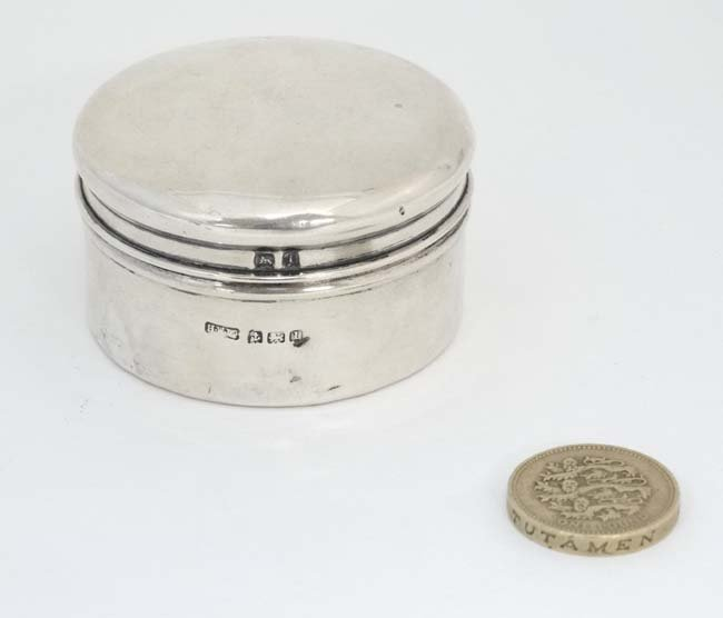 A silver pot and cover with paper pin tape coil within.