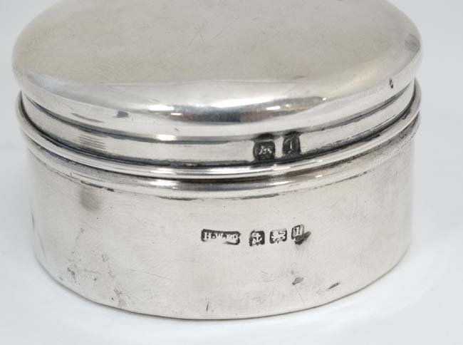 A silver pot and cover with paper pin tape coil within. - 2