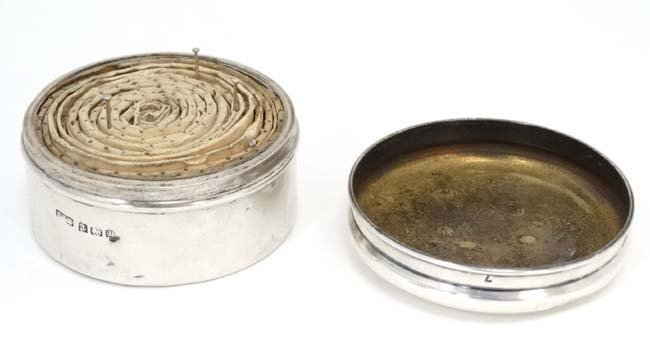 A silver pot and cover with paper pin tape coil within. - 3