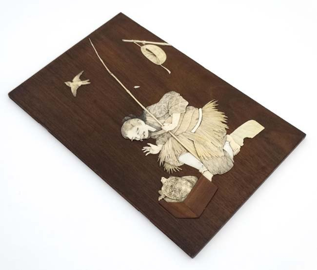 A 19thC Japanese hardwood plaque with ivory and mother