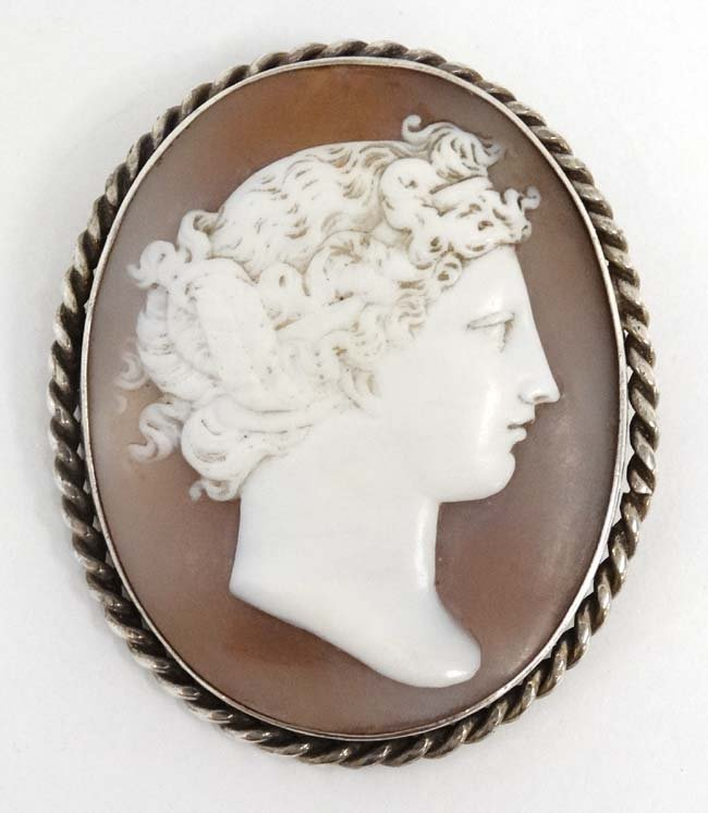 A classical carved shell cameo in a white metal mount