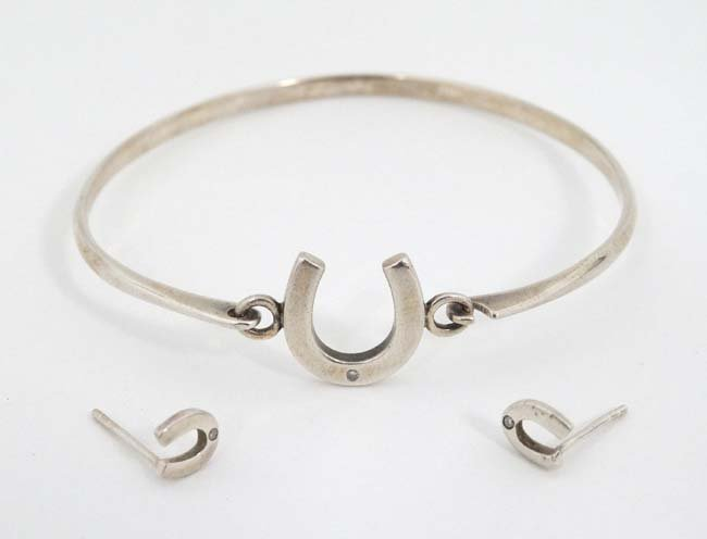 A silver bracelet and matching earnings with horseshoe