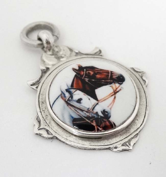 A hallmarked silver fob with later applied ceramic