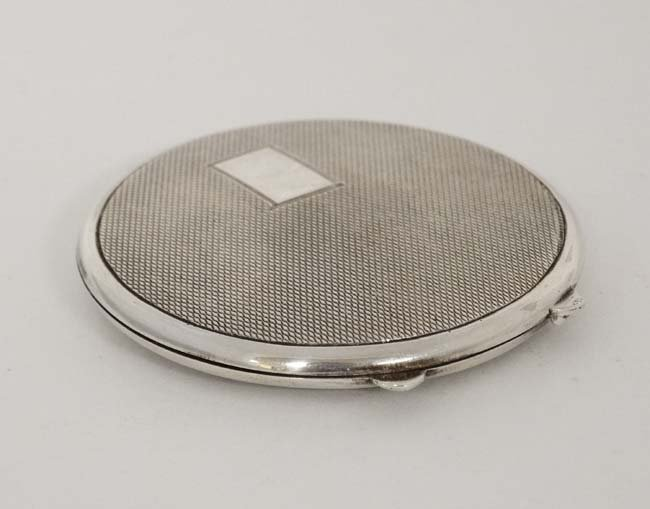 A silver powder compact with engine turned decoration. - 2